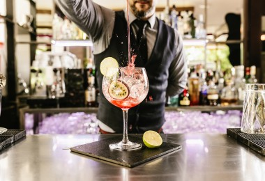 Expert barman is making cocktail at night club. Barcelona